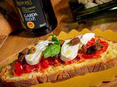 Bruschetta Burratina con pomodorini freschi brurratina olive taggiasche basilico e olio EVO Garbo Redoro