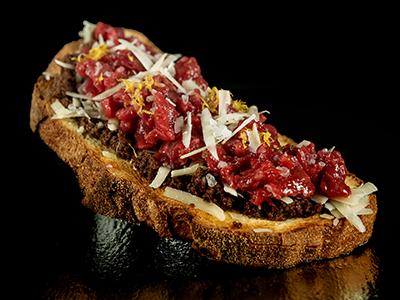 Bruschetta con Tartare di Manzo olivella nera e scaglie di grana